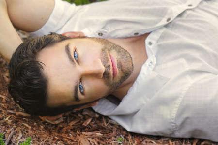 屋外屋外でリラックスしたカジュアルなの白いシャツに非常にハンサムな顔で若い男の肖像