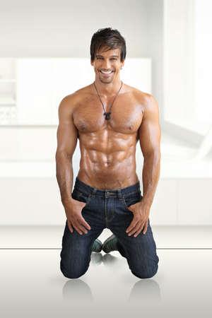 Sexy smiling shirtless male model flirting against white modern studio background photo