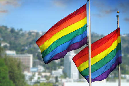 A pair of rainbow flags waving in wind against city background of West Hollywood, California