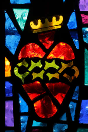Detail of a church stained glass showing a heart with crown photo