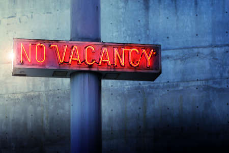 Glowing retro neon no vacancy sign against cool blue wall background