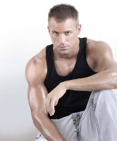 exercise man: Good looking young muscular masculine man with great arms against neutral background Stock Photo