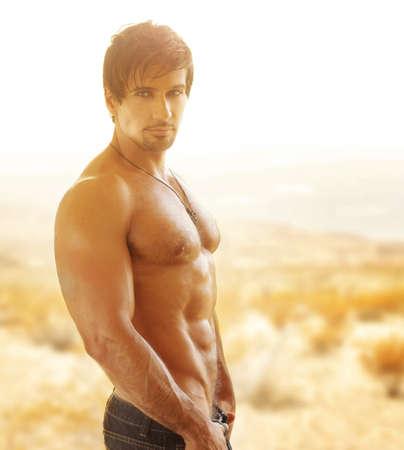 hombres musculosos: Hombre muscular atractivo con gran cuerpo al aire libre en la luz dorada