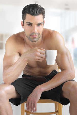 Portrait int?rieur d'une chaude jeune mod?le masculin d?tendu heureux avec une tasse de caf? du matin