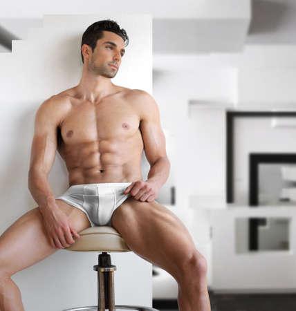 Très sexy, jeune homme! D'ajustement en lingerie blanche dans un cadre intérieur moderne et contemporain Banque d'images