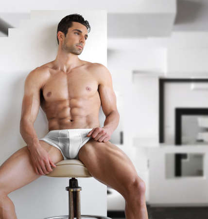 erotic male: Very sexy young fit manl in white underwear in modern contemporary interior setting Stock Photo