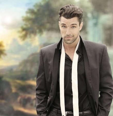 Fashion Portret van een jonge mannelijke model in zwart pak met witte das tegen elegante achtergrond