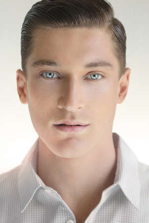 Close up portrait of young handsome man against neutral background in white shirt