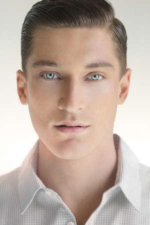 Close-up portret van jonge knappe man tegen neutrale achtergrond in wit overhemd