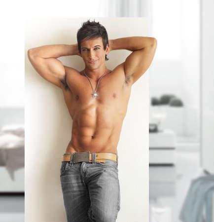 Sexy modèle masculin torse nu sourire avec un corps musclé et abs dans un cadre moderne et contemporain