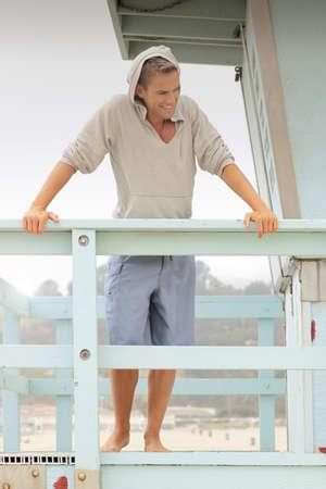 Retrato de una joven modelo masculino en pantalones cortos y jersey caliente relaja en el establecimiento de playa al aire libre Foto de archivo - 22529432