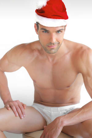 Muscular handsome sexy Santa Claus in red hat and white underwear against white background Stock Photo