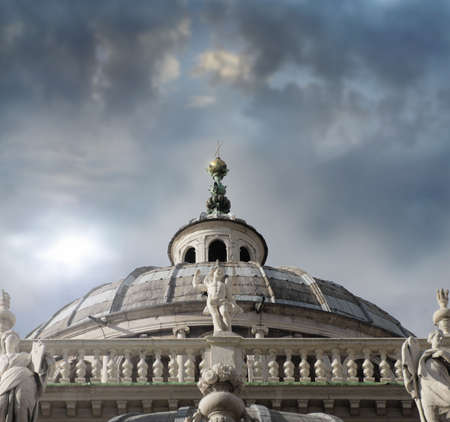 Detail of dome at Italian cathedral with marble statues and cross on top with dramatic skyscape