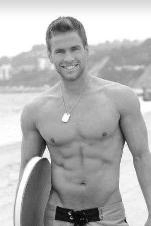 Portrait d'un jeune homme musclé actif à la plage avec planche de surf