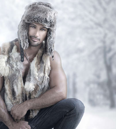 Fashion portrait of male model wearing fur in winter wonderland