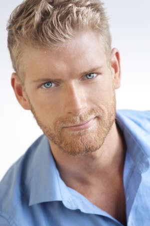 blonde yeux bleus: Close-up portrait d'un beau jeune homme sur fond blanc neutre Banque d'images