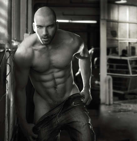 Erotic portrait of a muscular  man in industrial garage setting