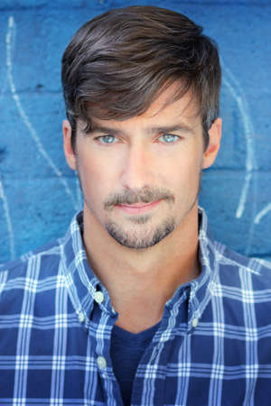 Close up portrait of a handsome man in blue shirt with blue eyes against blue background Foto de archivo