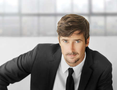 Bright portrait of an attractive smart young businessman in mondern office setting Foto de archivo