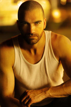 Classic portrait of a sexy moody man in golden light and shadow