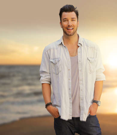 Romantic portrait of a great looking young guy relaxing with big beaming smile at the beach at sunset