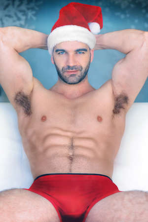 Sexy hunk Santa in red underwear and cap sitting against winter