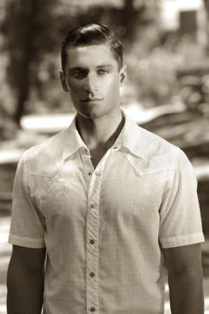 Elegant cute young male model posing outside in classic sepia tones