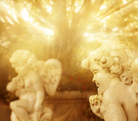 Fantastical portrait of angelic cherub statues with rays of golden light Banque d'images