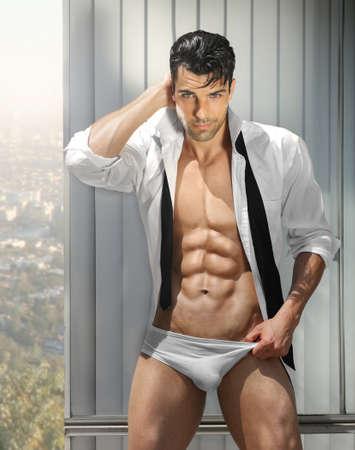 Beau modèle masculin musculaire en révélant mémoires dans provocante pose avec la chemise ouverte