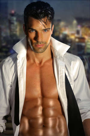 nudo maschile: Sensuale ritratto di un uomo muscoloso molto bello con la camicia aperta e il corpo caldo contro la finestra di notte