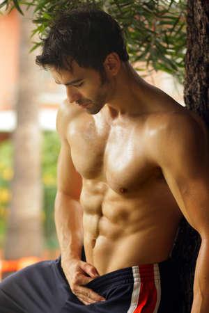 Hot sexy fit man leunend tegen boom