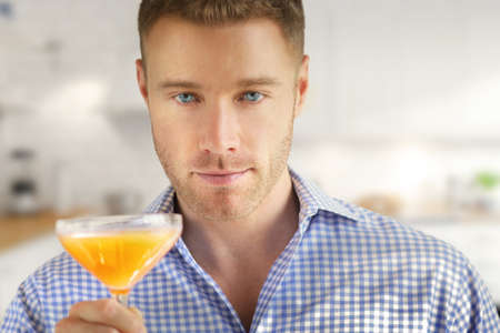 Handsome young man holding a cocktail