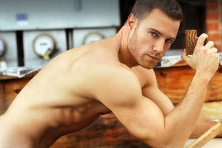 Sexy macho guy shirtless holding working with wood photo