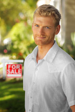 Young attractive man outdoors in front of for sale home sign Banco de Imagens