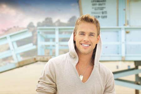 해변에서 큰 미소를 가진 젊은 잘 생긴 남자의 야외 초상화
