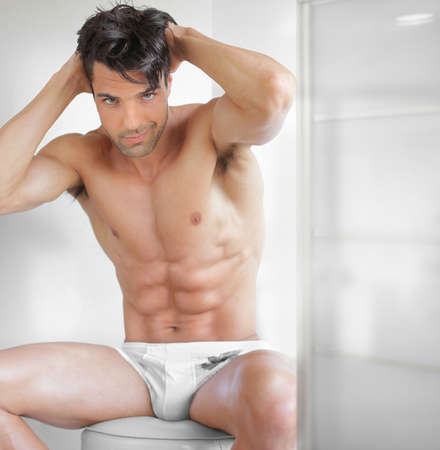 Portrait of a fit sexy male model in underwear in modern setting photo