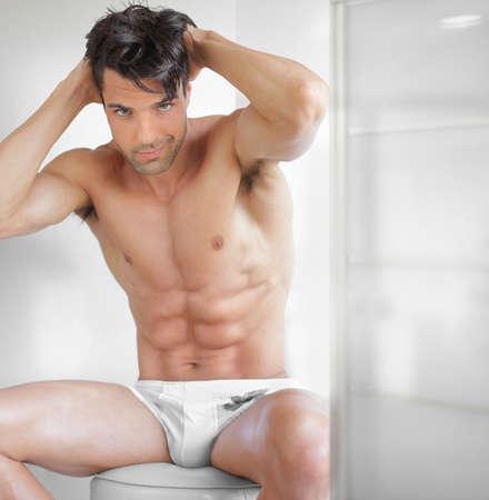 modelos hombres: Retrato de un modelo masculino del ajuste atractivo en ropa interior en un entorno moderno