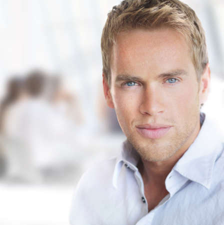 Bright portrait of a young good-looking successful businessman in office setting Banco de Imagens