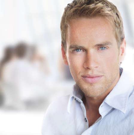Portrait lumineux d'un jeune beau homme d'affaires prospère en environnement de bureau