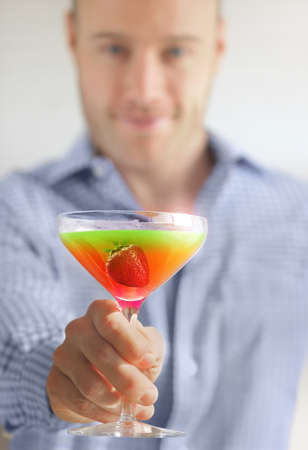 Blurred man holding up a colorful cocktail with focus on drink Banque d'images