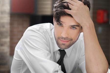 Portret van een ontspannen jonge man met speelse sexy grijns