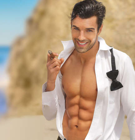 Sexy muscular handsome man with big smile and open shirt holding cigar photo