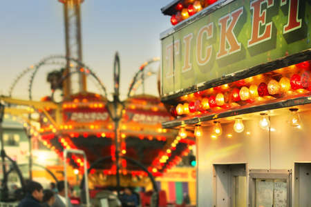 Scene at a classic carnival with rides and focus on ticket booth with subtle retro styling