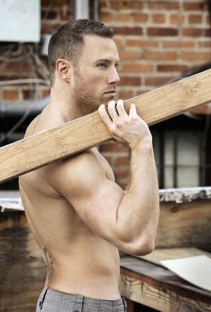buff: Sexy macho guy shirtless holding working with wood