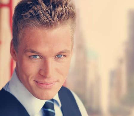 Jeune homme d'affaires élégant beau avec le sourire chaleureux en virage subtil cru