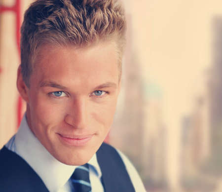 Young handsome stylish businessman with warm smile in subtle vintage toning
