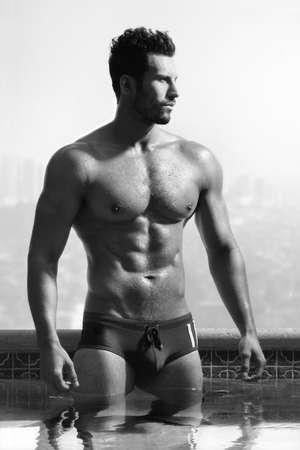 Portrait de mode classique d'un jeune sain beau macho man modèle athlète à la piscine