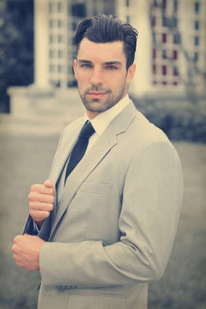 Handsome young businessman outdoors in stylish suit with overall subtle retro toning and feel Foto de archivo