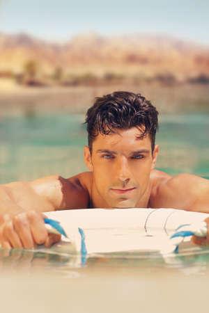 Sexy jeune homme de détente dans la piscine en plein air