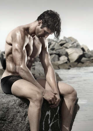 Portrait of a very muscular young man at beach sitting on rock looking down Stock Photo